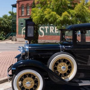 Downtown Brenham Ant Street Inn with antique car parked in front.
